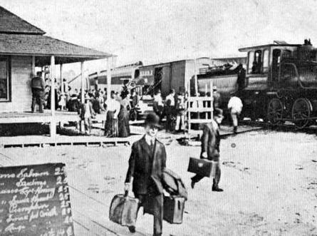 Passeggeri scendono dal treno, nel 1915. Le prime stazioni ferroviarie sono ormai corredate di tutto: guardate a lato il cartellone dei ..PREZZI!