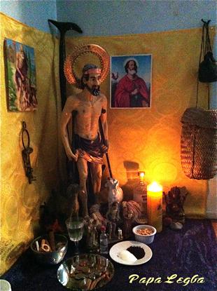 Un Papa Legba dei tempi nostri. Come vedete la mescolanza tra voodoo e Cristianesimo è evidente: la rassomiglianza col Cristo è messa ancora più in risalto dalla presenza dei disegni dei Santi Cristiani alle pareti. Tuttavia questa immagine sacra è un Loa Haitiano.