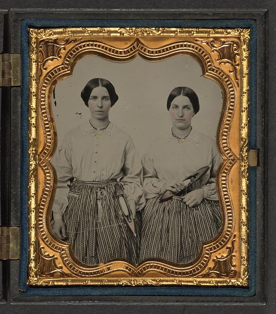 Sisters Lucretia Electa and Louisa Ellen Crossett in identical skirts, blouses, and jewelry with weaving shuttles 1859
